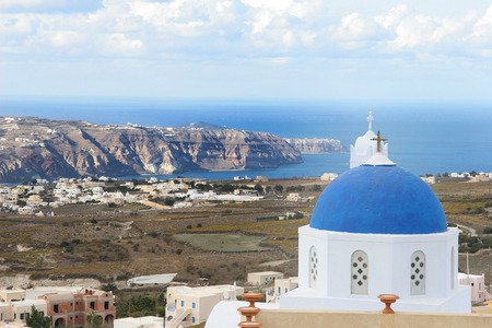 Traditional white church with a Blue dome, with island landscape behind, Santorini, Greece. photo