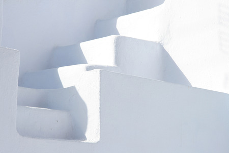 greece: Minimal white stone staircase between two white walls, Oia, Santorini, Greece.