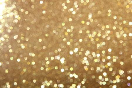 Gold abstract glitter background made up of a gold background with white, cream, yellow & beige circles of glitter across the frame which is defocused.