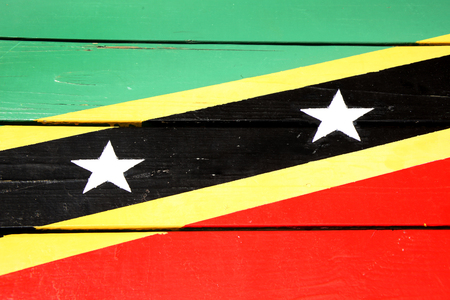 Flag of St Kitts & Nevis painted on wooden planks, in bright colours of red, yellow, green & black. Stock Photo
