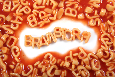 The word 'Brainstorm' written in alphabetti spaghetti, orange pasta shaped letters.