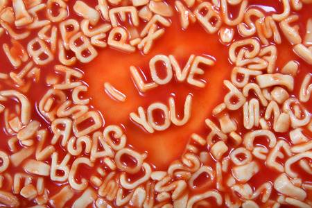 i Love you text written in Alphabetti Spaghetti pasta shaped letters, with tomato sauce around it.