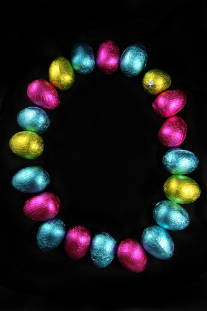 Colorful foil wrapped easter eggs laid out in the oval shape of an egg, on a black background.