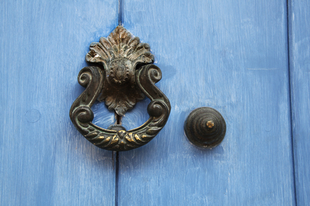 Traditional ornate door handle or knocker against a blue painted wooden door, Cartagena, Colombia. Stock Photo