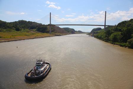 Tug boat sailing towards the Centennial Bridge, on the Culebra Cut, Panama Canal. 写真素材