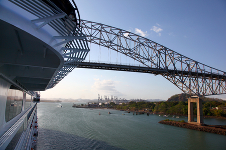 Cruise ship passing under the Bridge of the Americas, with a major shipping port in the background, Panama Canal.