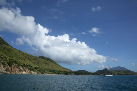 View of the coastline from the sea with a sailing boat, St Kitts, Caribbean.