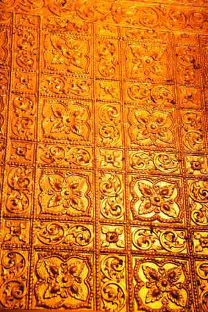 Close up of a golden wall designed with flowers inside the Buddhist Botataung pagoda, Yangon, Myanmar. Stock Photo