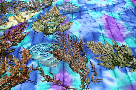 Colourful fabric with leaves, ferns & paper shapes cut out demonstraiting how to create tie dye designs, Bora Bora, French Polynesia.