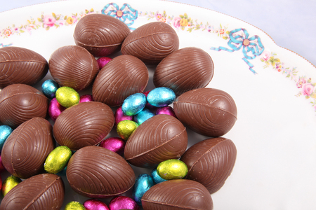 Chocolate easter eggs & colourful foil wrapped eggs on a white plate with a traditional flower design.