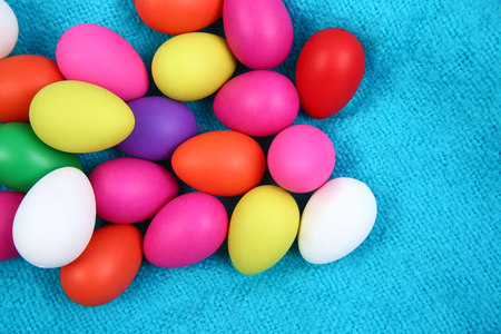 Multi colored easter eggs against a bright blue wool blanket background.