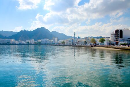 Waterfront of the city of Muscat, Oman, with buildings in the foreground & surrounded by mountains behind.
