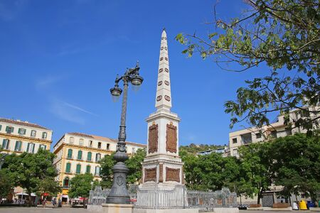General Torrijos Monument which is obelisk shaped & situated in the downtown city centre public square; Plaza de la Merced, Malaga, Andalusia, Southern Spain.