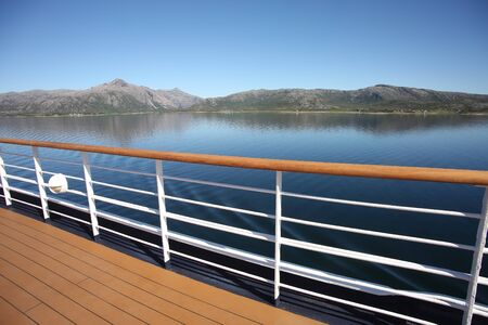 Deck & railing of a ship as it cruises fjords, islands & inside passages; the Andfjorden & Vestfjorden, between Bodo & Hammerfest, Norway.