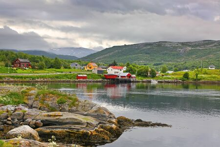 Beautiful landscape along with waters edge, with a village & church & mountains in the background, Saltstraumen, Municipality of Bodo, Nordland county, Norway.