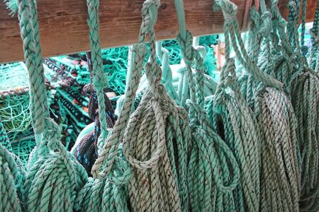 Close up of green blue turquiose rope Hanging up on wood used for fishing or sailing, Norway.