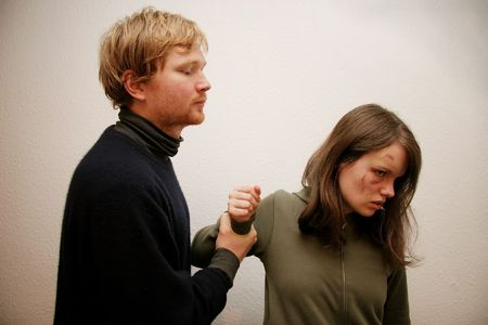 beat women: A couple arguing. The woman, with an injury on her cheek, has been beaten. Stock Photo