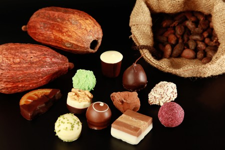 Various chocolate truffles, cocoa pods and cocoa beans in a sack. photo
