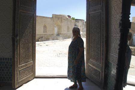 60 65: Uzbek elderly woman on a background of ancient doors