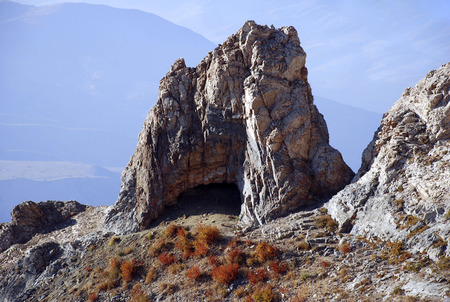 Cliff with a cave in the mountains of Tien Shan. Uzbekistan Stock Photo