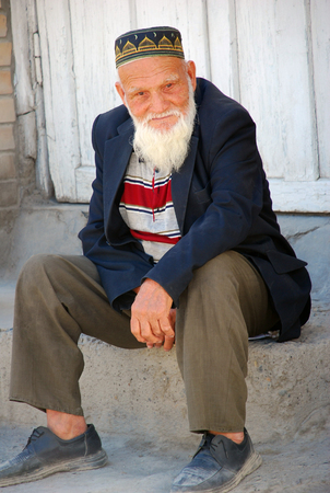 60 65: Elderly Uzbek - grandfather sitting on a stone