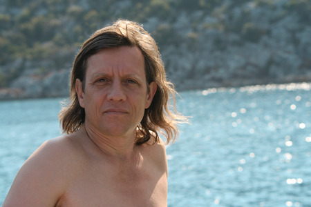 60 65: An elderly man with long hair lit by the bright sun