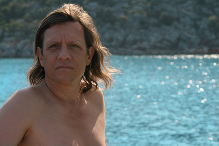 60 65: A man with long hair in the sea Stock Photo