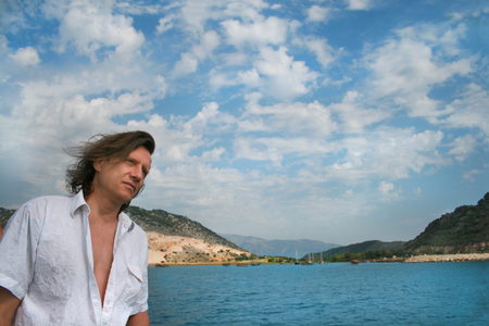 A man with long hair on a background of the sea, islands and clouds