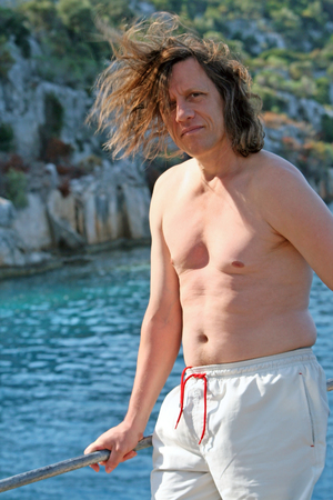 A man with long hair in the sea Stock Photo