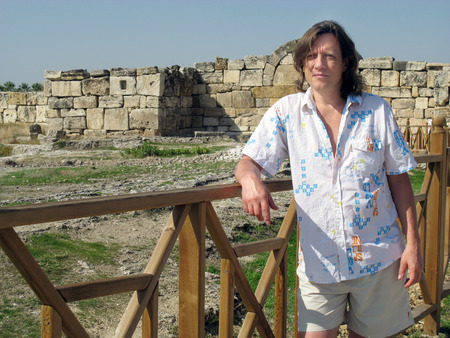 The man - a tourist stands near the ruins and fences