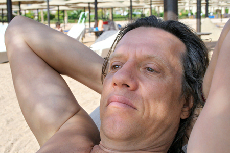 age 60: Man resting on the beach and looks into the distance