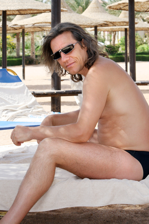 looked: Man sitting sideways on the beach with sunglasses