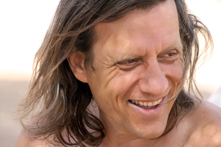 age 60: A man with long hair smiling