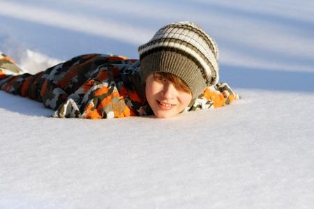 Boy lying in the snow