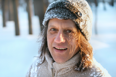 Happy man with long hair in the park in winter