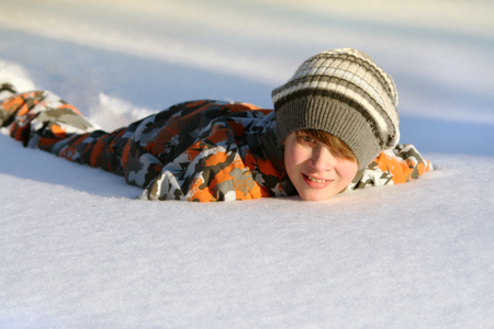 Boy lying in the snow