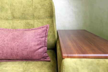 Fragment of a green sofa with a wooden armrest and a pink pillow Stock Photo