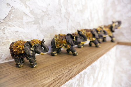 Figurines of elephants on the shelf (luck, happiness in the house). Elephants with hides made of natural amber
