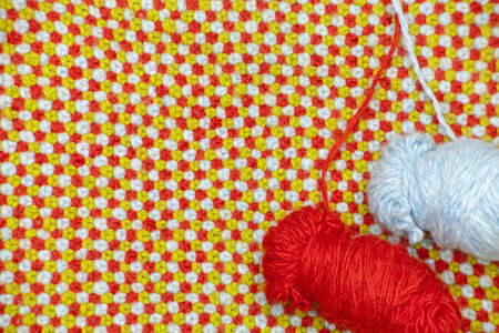 A tangle of red and blue yarns on a background of knitted cloth with red, blue and green wool Stock Photo