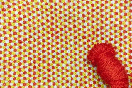 A tangle of red, woolen yarn on a background of knitted, woolen cloth Stock Photo