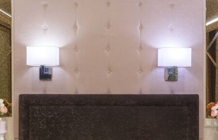 Two sconces burn on a soft wall at the head of the bed. Modern design and decor