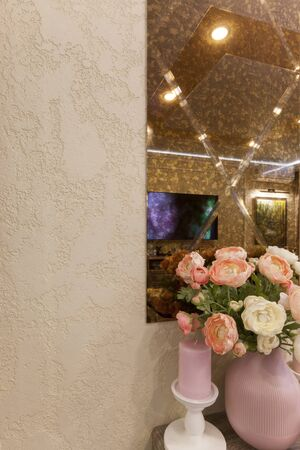 A fragment of the interior in the apartment. Wall with a mirror and stucco. Modern design and decor