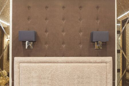 A soft wall and 2 sconces at the head of the bed between 2 mirrors - a symmetrical design