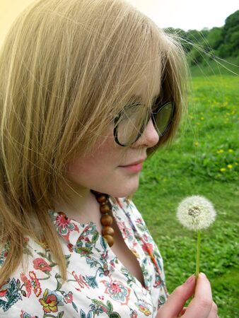 Girl with glasses on the lawn with a dandelion