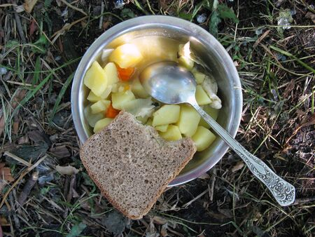 Modest food on a hike - stewed potatoes in an iron bowl and Russian, brown bread