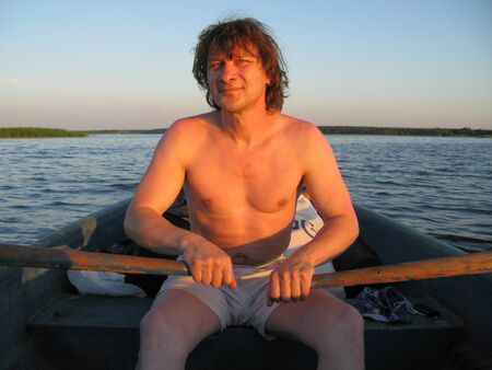 A man rowing oars in a boat at sunset. Russia. Volga river