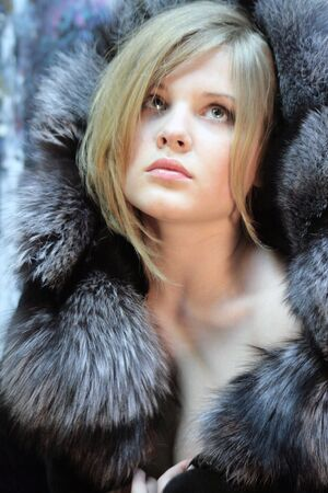 teenage girl looking up. Natural blonde with long hair in a chic silver fox fur coat
