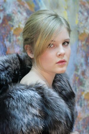 girl - teenager, natural blonde in a chic fur coat from silver fox