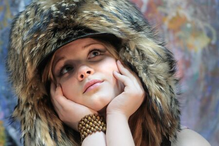 Portrait of a pensive teenage girl in a chic fur hat - earflaps