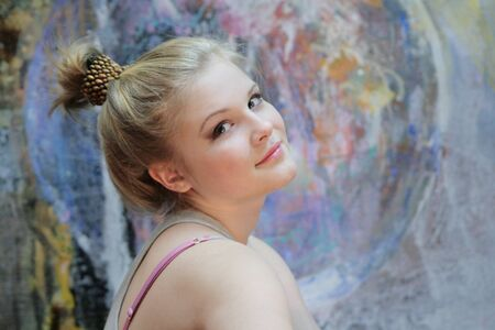 Portrait of a natural blonde, teenage girls with light makeup on a colored background. Russian